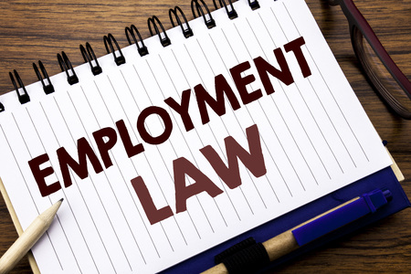 Hand writing text caption inspiration showing Employment Law. Business concept for Employee Legal Justice Written on notebook paper, wooden background with glasses pen and marker.