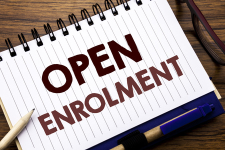 Hand writing text caption inspiration showing Open Enrolment. Business concept for Medicine Doctor Enroll Written on notebook paper, wooden background with glasses pen and marker.