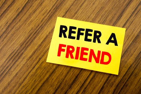 Hand writing text caption inspiration showing Refer A Friend. Business concept for Referral Marketing written on sticky note paper on wooden keyboard background. Empty table. Foto de archivo