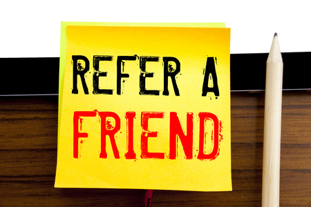 Hand writing text caption inspiration   Refer A Friend. Business concept for Referral Marketing written on sticky note paper on wooden and tablet background.