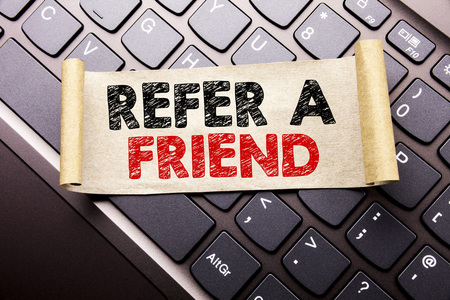 Hand writing text caption inspiration showing Refer A Friend. Business concept for Referral Marketing written on sticky note paper on dark keyboard background.