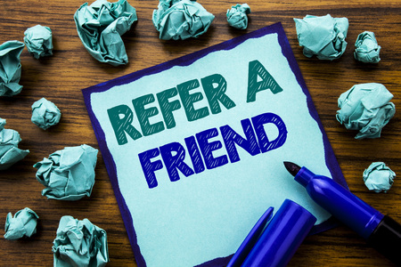 Writing text showing Refer A Friend. Business concept for Referral Marketing Written on sticky note paper, wooden background marker folded yellow paper meaning thinking 스톡 콘텐츠