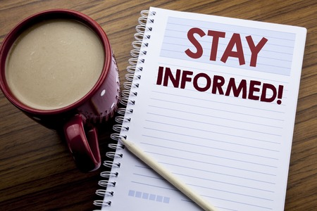 Hand writing text caption inspiration showing Stay Informed. Business concept for Be Awareness Or Awake written on note paper notepad on the wooden background with coffee and pen. Foto de archivo