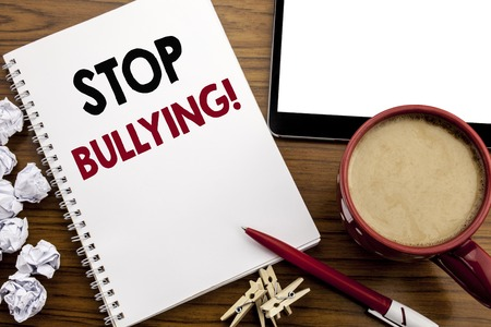 Conceptual hand writing text caption inspiration showing Stop Bullying. Business concept for Prevention Problem Bully written on notepad paper on the wood table with coffee in office Stock Photo