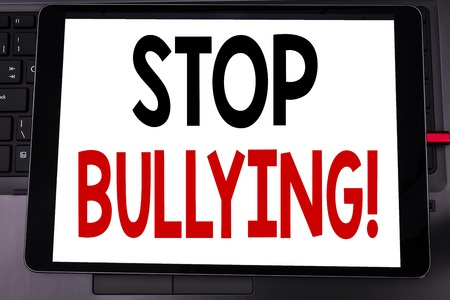 Conceptual hand writing text caption inspiration showing Stop Bullying. Business concept for Prevention Problem Bully written on tablet laptop on black keyboard background.