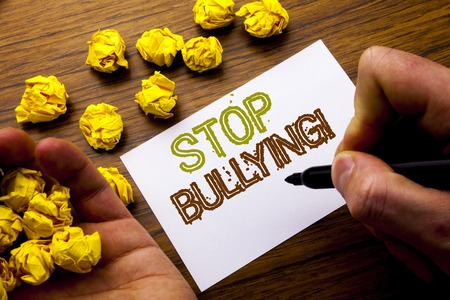 Word, writing Stop Bullying. Concept for Prevention Problem Bully written on notebook note paper on wooden background with folded paper meaning thinking for idea. Man hand and marker.