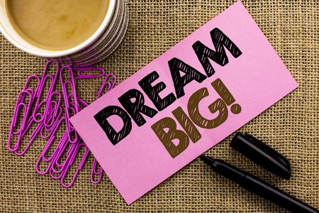 Handwriting text writing Dream Big. Concept meaning Motivation Plan Aim Dream Vision Strategy Challenge Idea written Pink Sticky Note Paper the jute background Coffee Cup Pen Pins.