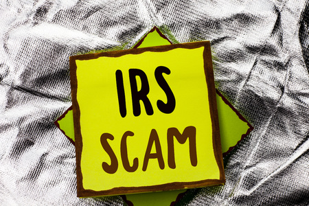 Text sign showing Irs Scam. Conceptual photo Warning Scam Fraud Tax Pishing Spam Money Revenue Alert Scheme written Stacked Sticky Note Paper the Silver textured background. Stock Photo