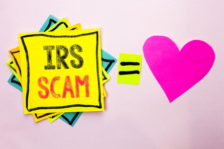 Text sign showing Irs Scam. Conceptual photo Warning Scam Fraud Tax Pishing Spam Money Revenue Alert Scheme written Stacked Sticky Note Papers the plain background with Heart next to it.