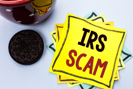 Writing note showing  Irs Scam. Business photo showcasing Warning Scam Fraud Tax Pishing Spam Money Revenue Alert Scheme written Yellow Sticky Note Paper the plain background Cup.
