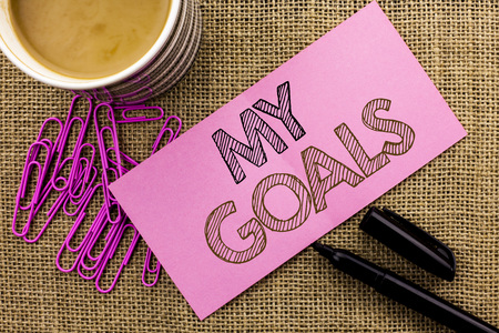 Handwriting text writing My Goals. Concept meaning Goal Aim Strategy Determination Career Plan Objective Target Vision written Pink Sticky Note Paper the jute background Coffee Cup Pen Pins.