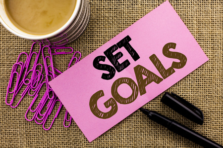 Handwriting text writing Set Goals. Concept meaning Target Planning Vision Dreams Goal Idea Aim Target Motivation written Pink Sticky Note Paper the jute background Coffee Cup Pen Pins.