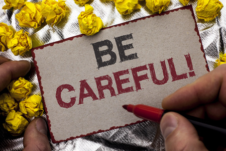 Conceptual hand writing showing Be Careful. Business photo showcasing Caution Warning Attention Notice Care Beware Safety Security written by Man Holding Marker Cardboard textured background Stok Fotoğraf