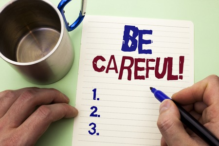 Writing note showing  Be Careful. Business photo showcasing Caution Warning Attention Notice Care Beware Safety Security written by Man Notebook Paper Holding Marker plain background Cup.