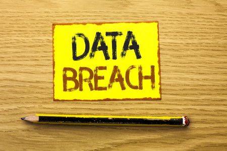 Conceptual hand writing showing Data Breach. Business photo showcasing Stolen Cybercrime Information Hacking Security Malicious Crack written Yellow Sticky Note wooden background Pencil.
