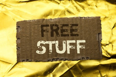 Word writing text Free Stuff. Business concept for Complementary Free of Cost Chargeless Gratis Costless Unpaid written tear Cardboard Piece the Golden textured background.