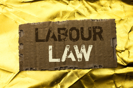 Word writing text Labour Law. Business concept for Employment Rules Worker Rights Obligations Legislation Union written tear Cardboard Piece the Golden textured background. Banque d'images