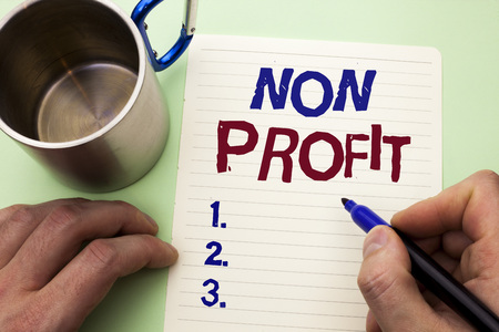Writing note showing  Non Profit. Business photo showcasing Charitable Wrothless Philanthropy Aid Unlucrative Profitless written by Man Notebook Paper Holding Marker plain background Cup.