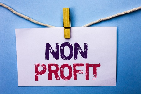 Text sign showing Non Profit. Conceptual photo Charitable Wrothless Philanthropy Aid Unlucrative Profitless written White Note Paper hanging with rope the plain background Clip. Stock Photo
