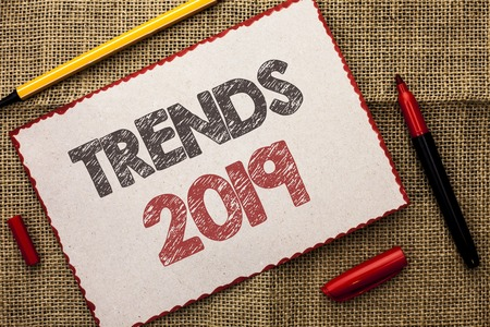 Writing note showing  Trends 2019. Business photo showcasing Current Movement Latest Branding New Concept Prediction written Cardboard Piece the jute background Markers next to it. Banco de Imagens