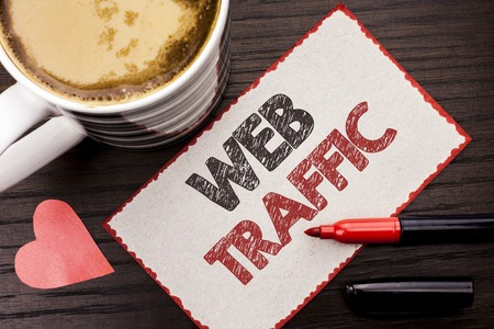 Text sign showing Web Traffic. Conceptual photo Internet Boost Visitors Audience Visits Customers Viewers written Sticky Note the wooden background Coffee Cup Heart Marker next to it.