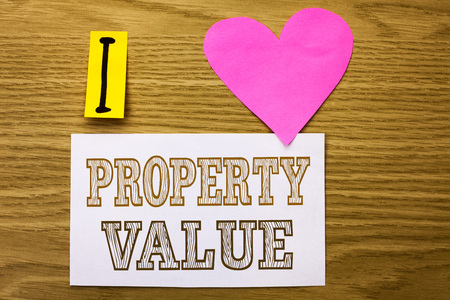 Word writing text Property Value. Business concept for Estimate of Worth Real Estate Residential Valuation written Sticky Note Paper the wooden background Pink Heart next to it.