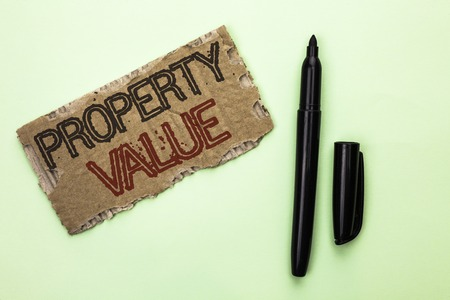 Word writing text Property Value. Business concept for Estimate of Worth Real Estate Residential Valuation written Tear Cardboard Piece the plain background Marker next to it.