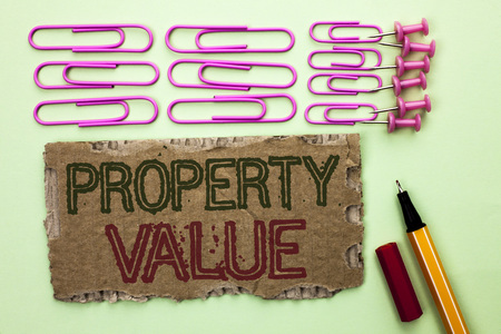 Handwriting text writing Property Value. Concept meaning Estimate of Worth Real Estate Residential Valuation written Tear Cardboard Piece plain background Marker and Pins next to it.