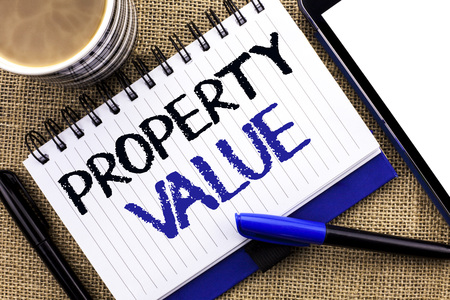 Text sign showing Property Value. Conceptual photo Estimate of Worth Real Estate Residential Valuation written Notebook Book the jute background Tablet Coffee Cup and Pens next to it
