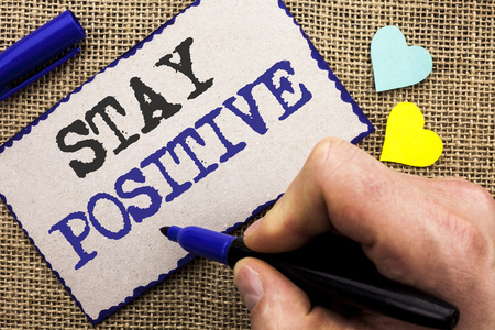 Conceptual hand writing showing Stay Positive. Business photo showcasing Be Optimistic Motivated Good Attitude Inspired Hopeful written Sticky Note the jute bakground with Love Hearts. Stock Photo