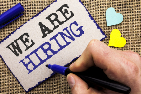 Conceptual hand writing showing We Are Hiring. Business photo showcasing Talent Hunting Job Position Wanted Workforce HR Recruitment written Sticky Note the jute background with Love Hearts.