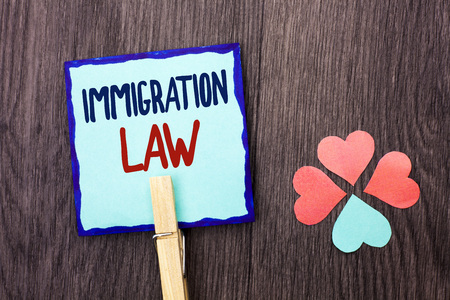 Handwriting text writing Immigration Law. Concept meaning National Regulations for immigrants Deportation rules written Sticky Note Paper Holding With Clip the wooden background Hearts. Stok Fotoğraf