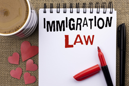 Conceptual hand writing showing Immigration Law. Business photo showcasing National Regulations for immigrants Deportation rules written Notebook Book the jute background Cup Hearts Pen
