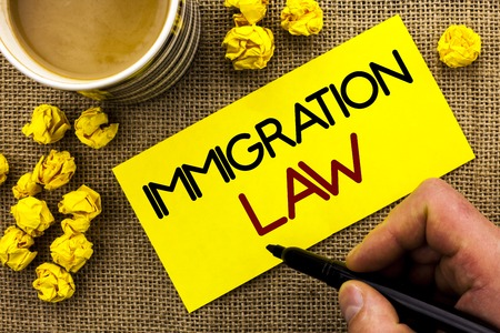 Text sign showing Immigration Law. Conceptual photo National Regulations for immigrants Deportation rules written Sticky Note Paper the jute background Cup and Paper Balls next to it.