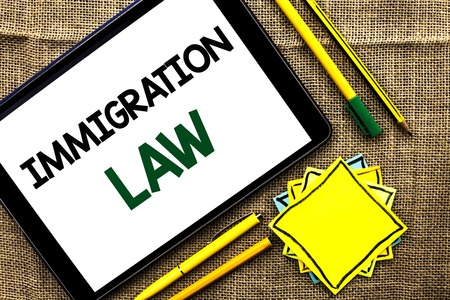 Text sign showing Immigration Law. Conceptual photo National Regulations for immigrants Deportation rules written Tablet the jute background Pens Pencil and Sticky Note Papers