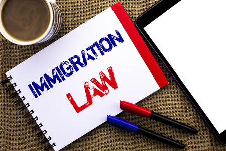Handwriting text Immigration Law. Concept meaning National Regulations for immigrants Deportation rules written Notebook Book the jute background Tablet Coffee Cup and Pens next to it.