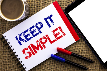 Handwriting text Keep It Simple Motivational Call. Concept meaning Simplify Things Easy Clear Concise Ideas written Notebook Book the jute background Tablet Coffee Cup and Pens next to it.