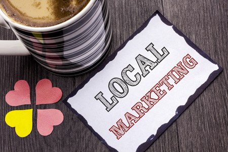Handwriting text Local Marketing. Concept meaning Regional Advertising Commercial Locally Announcements written Sticky Note Paper the wooden background Coffee Cup and Heart next to it. Stock Photo