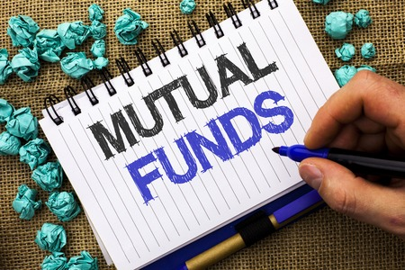 Word writing text Mutual Funds. Business concept for Investment Strategy to purchase shares with other investors written by Man Holding Marker Notebook Book the jute background.