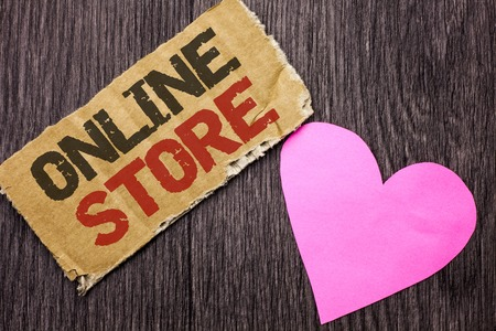 Handwriting text Online Store. Concept meaning Internet related business Website where you can buy in the net written Cardboard Piece the wooden background with Love Heart.