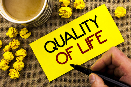Text sign showing Quality Of Life. Conceptual photo Good Lifestyle Happiness Enjoyable Moments Well-being written Sticky Note Paper the jute background Cup and Paper Balls next to it.