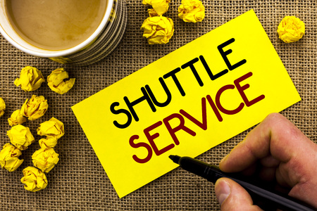 Text sign showing Shuttle Service. Conceptual photo Transportation Offer Vacational Travel Tourism Vehicle written Sticky Note Paper the jute background Cup and Paper Balls next to it. Stock Photo