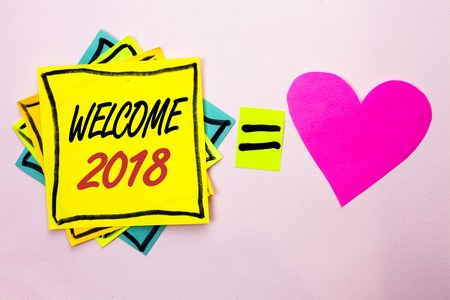Text sign showing Welcome 2018. Conceptual photo Celebration New Celebrate Future Wishes Gratifying Wish written Yellow Sticky Note Paper the plain background Pink Heart next to it.