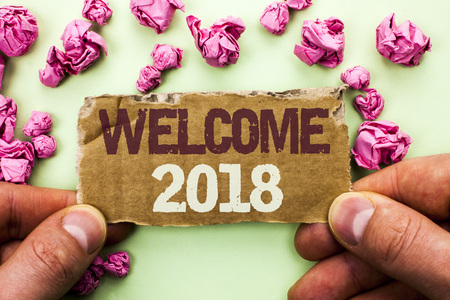 Word writing text Welcome 2018. Business concept for Celebration New Celebrate Future Wishes Gratifying Wish written Tear Cardboard Piece Holding by Man the plain background.