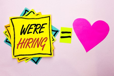 Text sign showing Were Hiring. Conceptual photo Recruiting Hiring Now Recruitment Vacancy Announced Hire written Yellow Sticky Note Paper the plain background Pink Heart next to it. Stock Photo