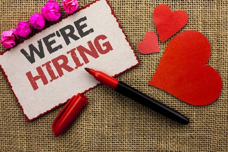 Word writing text Were Hiring. Business concept for Recruiting Hiring Now Recruitment Vacancy Announced Hire written Cardboard Piece the jute background Marker and Hearts next to it.