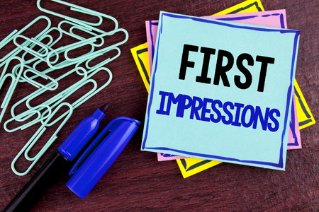 Handwriting text First Impressions. Concept meaning Encounter presentation performance job interview courtship written Sticky Note Paper wooden background Marker and Paper Clips next to it.
