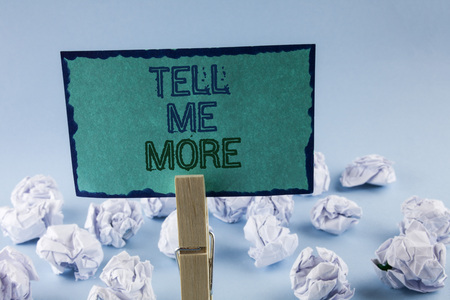 Text sign showing Tell Me More. Conceptual photo Elaborate your business thoughts further for assistance written Sticky Note Paper holding by Clip plain background White Paper Balls