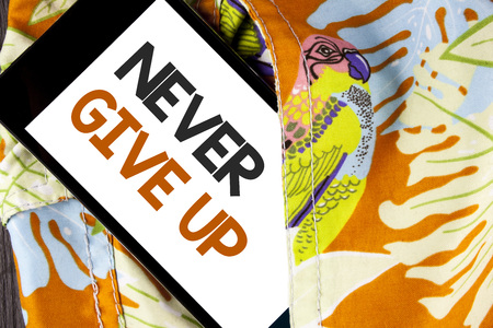 Conceptual hand writing showing Never Give Up. Business photo text Be persistent motivate yourself succeed never look back written Mobile Phone Screen the printed fabric background. Stock Photo