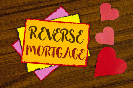 Text sign showing Reverse Mortgage. Conceptual photo Elderly homeowner retirement option regular payment benefit written Sticky note paper wooden background Hearts next to it. Stock Photo